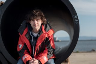 Boyan Slat sits in a floater segment of the first cleanup system on the assembly yard, April 2018.