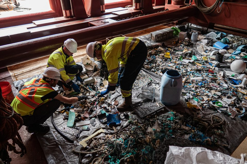 Crew sorting plastic into size and type classes onboard the support vessel during the System 001/B mission, 2019