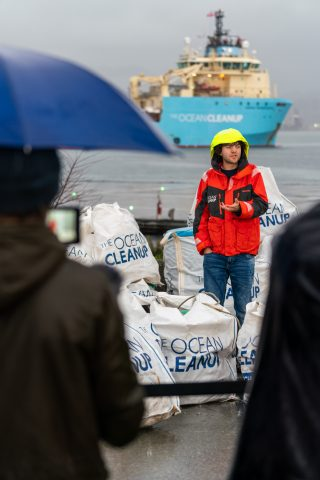 Boyan Slat standing with first plastic catch onshore at end of the System 001/B testing. The press conference was in Vancouver, Canada, in December 2019.