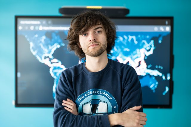 Boyan Slat, Founder & CEO, standing in front of The Ocean Cleanup's 1000 rivers pollution map
