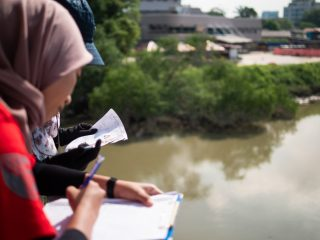 Volunteers counting and categorizing passing river pollution in Malaysia